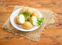 Aardappels in hun die huiden worden met kruiden op schotel worden verfraaid gekookt die Stock Fotografie