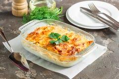 Aardappels met kaas, appelen en groenten worden gebakken die Stock Foto