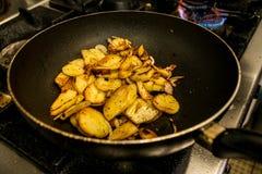 Aardappels in olie in een pan met kruiden voor autrian voedsel worden gebraden dat Royalty-vrije Stock Afbeelding