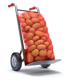 Aardappels in rode jutezakken op de handvrachtwagen Stock Foto