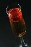 Aardbei in champagne tegen donkere achtergrond Stock Fotografie