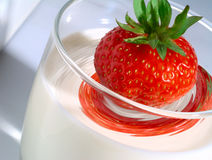 Aardbei die zich in glas melk werpt Stock Afbeeldingen