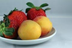 Aardbei en perziken op een plaat Stock Afbeelding