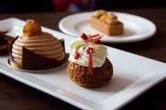 Aardbei-rabarber-vanille roomrookwolk en andere buitensporige gebakjes op platen Stock Foto