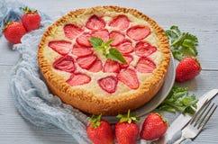 Aardbei scherp op de grijze keukenachtergrond Bessenkaastaart met organische verse aardbeien wordt verfraaid die royalty-vrije stock afbeelding