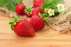 Aardbeien, bladeren en bloemen op houten oppervlakte bij selectief Stock Afbeeldingen