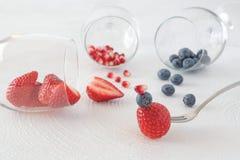 Aardbeien, bosbessen, granaatappel op wit en bessen op een vork stock foto
