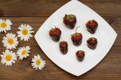 Aardbeien in chocolade op een witte vierkante plaat worden ondergedompeld die Houten achtergrond Hoogste mening Close-up royalty-vrije stock foto's