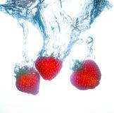Aardbeien die in water en het bespatten vallen Royalty-vrije Stock Fotografie