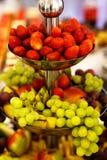 Aardbeien, druif en appelen voor op een gelaagde plaat worden gediend die Stock Foto
