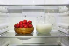 Aardbeien in een houten kom en een waterkruik melk op een plank in de ijskast stock afbeeldingen