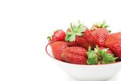 Aardbeien in een kom op wit wordt geïsoleerd dat Stock Foto's