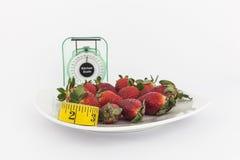 Aardbeien in een plaat met een gewichtsschaal Stock Afbeeldingen