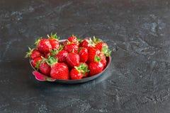 Aardbeien in een plaat op een donkere achtergrond Royalty-vrije Stock Afbeelding