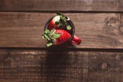 Aardbeien in een rode emailmok op een houten lijst stock afbeelding