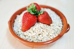 Aardbeien en havervlokken in een aardewerkkom Royalty-vrije Stock Foto