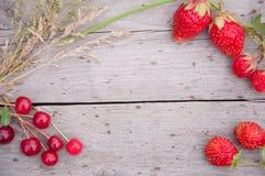 Aardbeien en kersen met gras op hout Stock Afbeelding
