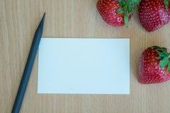 Aardbeien en notadocument op houten lijstachtergrond Stock Afbeelding