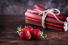 Aardbeien en rabarber op houten achtergrond stock afbeelding