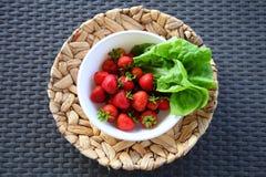 Aardbeien en sla in een kom op een rieten plaat Stock Foto's