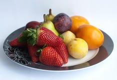 Fruit en bessen op een plaat Stock Foto