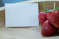 Aardbeien in houten kom en notadocument Stock Foto's