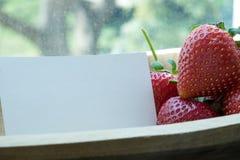 Aardbeien in houten kom en notadocument Royalty-vrije Stock Afbeeldingen