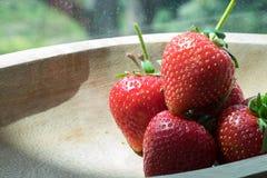 Aardbeien in houten kom en notadocument Stock Afbeelding