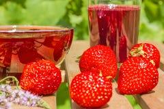 Aardbeien, jam en sap op de lijst in de tuin Royalty-vrije Stock Afbeelding