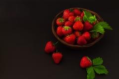 Aardbeien met bladeren in een mand op een donkere weefselbackgrou stock afbeelding