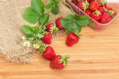 Aardbeien met bladeren en bloemen op houten oppervlakte en sackc Stock Foto