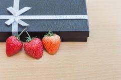 Aardbeien met zwarte giftdoos op houten achtergrond Royalty-vrije Stock Afbeeldingen