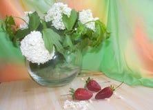 Aardbeien op een achtergrond van bloemen in een vaas Royalty-vrije Stock Fotografie