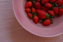Aardbeien op een roze plaat stock afbeelding
