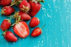 Aardbeien op een turkooise blauwe houten lijst Stock Foto's