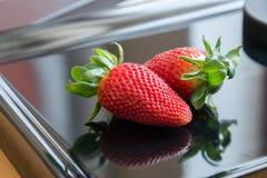 2 aardbeien op een zwarte achtergrond met bezinning Stock Foto