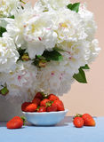 Aardbeien in schotel op achtergrond van witte pioenen Royalty-vrije Stock Fotografie