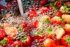 Aardbeien in water worden doorweekt dat stock afbeeldingen