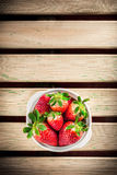 Aardbeien in witte ceramische kom op houten lijst Stock Foto