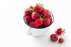 Aardbeien in witte emailmok stock afbeeldingen