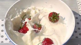 Aardbeiendaling in de witte die kom met verse melk wordt gevuld stock footage