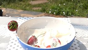 Aardbeiendaling neer aan de kom verse melk op de lijst stock videobeelden