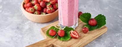 Aardbeimilkshake in een glaskruik en verse aardbeien met bladeren, lange banner royalty-vrije stock foto