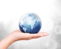 Aarde in menselijke hand tegen Stock Foto's