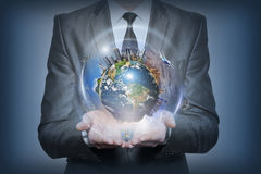 Aarde in menselijke handen op blauwe achtergrond Royalty-vrije Stock Fotografie