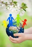 Aarde met familie in kinderen` s handen stock illustratie