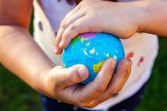 Aardebol in kinderenhanden stock afbeeldingen