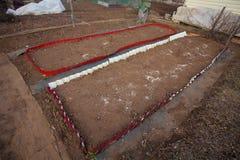 Aarden bedden met rode randen in tuin stock afbeeldingen