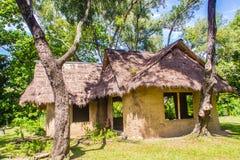 Aarden huis onder schaduw van bomen Een aardehuis, ook als aardeberm wordt bekend, aarde beschutte huis, of het eco-huis is een a stock afbeelding