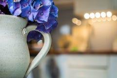 Aarden kop met hydrangea hortensia en vage keuken op achtergrond stock afbeeldingen